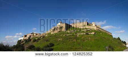 Panorama of Palmela castle seen from south below. Deep green grass slopes under a deep blue sky. Setubal Portugal.