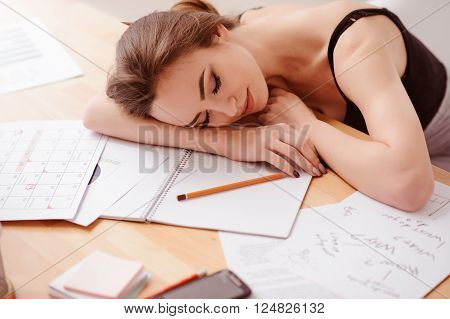 Time to rest. Charming content nice woman leaning on the table and sleeping while  being at work