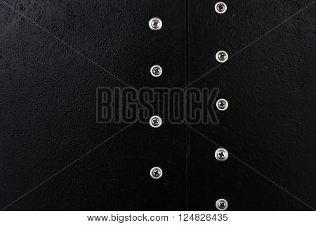 Black texture with two parallel lines of metal buttons.