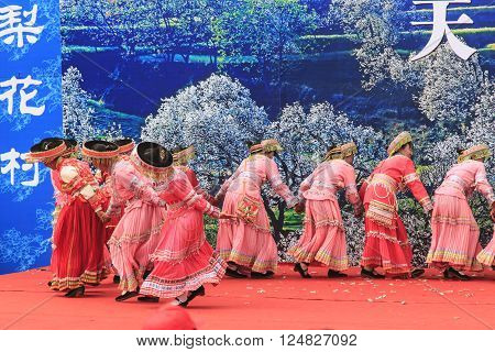 Heqing, China - March 15, 2016: Chinese women dressed with traditional clothing dancing and singing during the Heqing Qifeng Pear Flower festival.