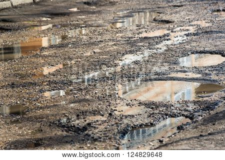 Potholes on the asphalt road filled with water