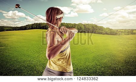Woman golfing in the summer over beautiful landscape background. Young active Caucasian female wearing sportswear playing golf on green field.