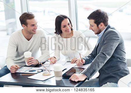 Friendly atmosphere. Cheerful positive delighted colleague sitting at the table and discussing project while expressing gladness
