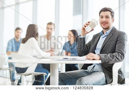 Relief stress. Cheerful positive handsome man sitting at the table and smiling while drinking coffee