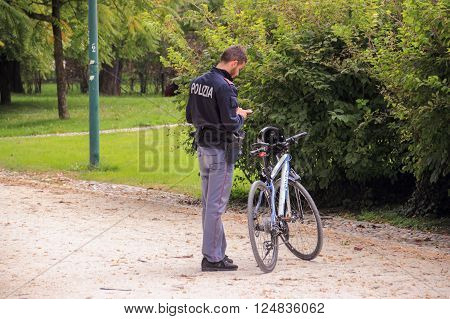 Milan, Italy - September 29, 2015: A police officer with a bicycle standing in a park and looking at mobile phone