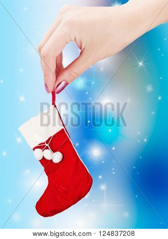 the hand holding a christmas sock on a blue background