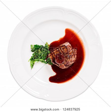 Delicious grilled fillet mignon steak with chard covered with red wine sauce. Isolated on a white background.