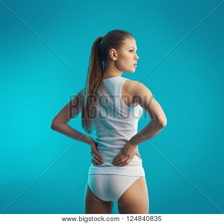 Lumbago. Back pain. Young attractive female holding her sore loin over blue background.