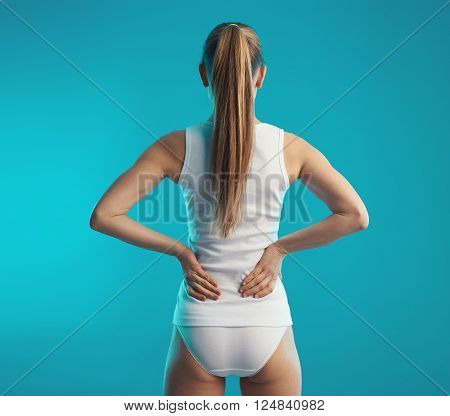 Backache on slender female body. Caucasian woman touching her loin in pain. Concept of back stretch and rehabilitation.