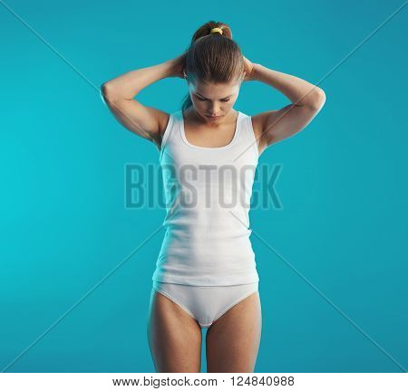 Young woman with muscular body doing therapeutical exercise for neck and back. Concept of body rehabilitation and therapy.