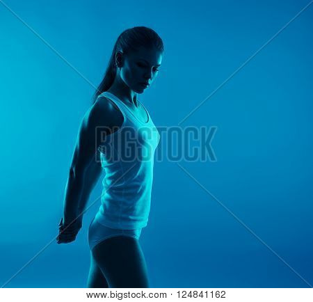 Back stretch. Muscles relaxation. Young sporty female exercising over blue background.