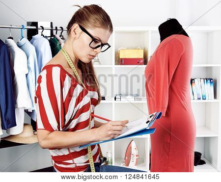 Female clothing designer drafting sketch of new trendy cotton dress sitting on the desk in atelier. Tailoring and handicraft concept.