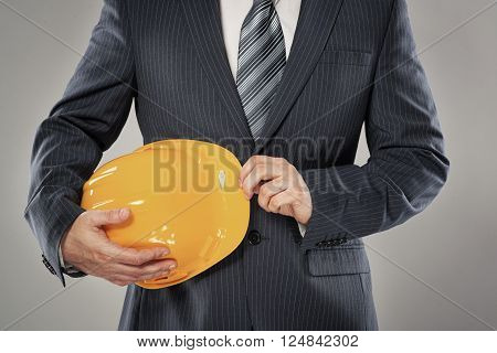 Male technician wearing business suit with safety helmet.