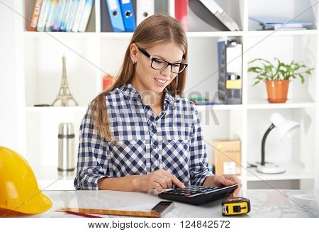 Woman accountant calculating architectural project cost in the office.
