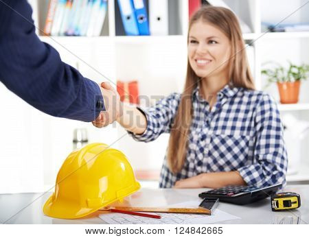 Businesspeople handshake. Young smiling female engineer meeting male customer in the office sitting at the table with tools, hardhat and calculator.