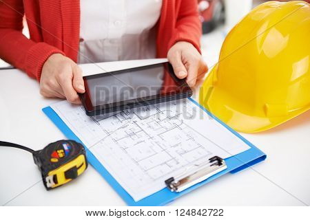 Close-up portrait of woman designer's hands using tablet pc in the office. Young female architect working on house sketch.