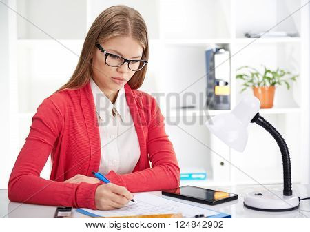 Female architect in eyeglasses measuring house blueprint at workplace. Young concentrated woman sitting at the desk with instruments, plan and tablet pc.