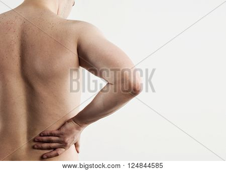 Portrait of young man suffering from spine disease over light grey background. Caucasian male having loin stretch.