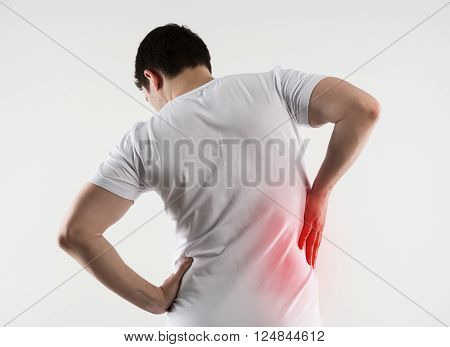 Hip or back injury. Young Caucasian man touching his hurt right side of body.