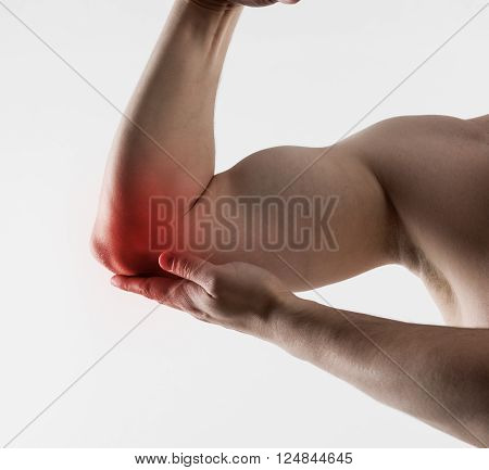 Man with chronic elbow pain. Closeup of male hand with red spot on painful zone over light grey background.