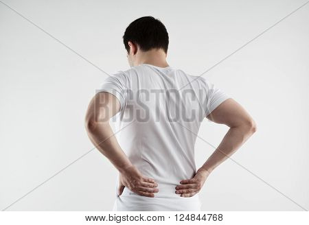 Back stretch. Young Caucasian man suffering from muscle inflammation and strain over light grey background.