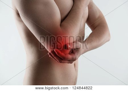 Sore pain of elbow. Sprain and arthritis symptoms. Young male touching his hurt arm over light grey background.