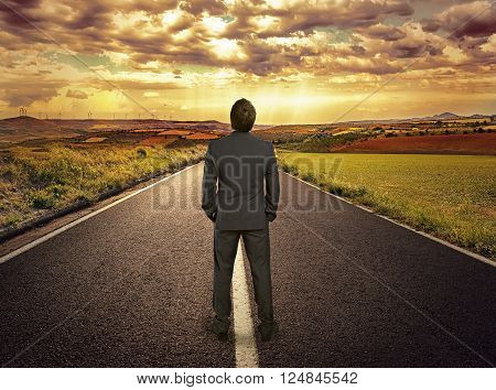 Portrait of businessman standing on asphalt road. Concept of straight path to progress, perspective and success.