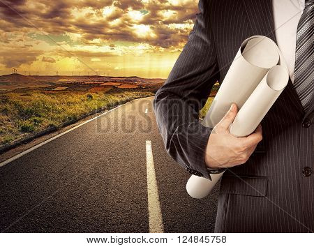 Male engineer with blueprints standing on straight road