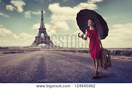 Paris. Eiffel tower. Young business woman hurrying up with luggage and umbrella on highway. Business trip to France concept.