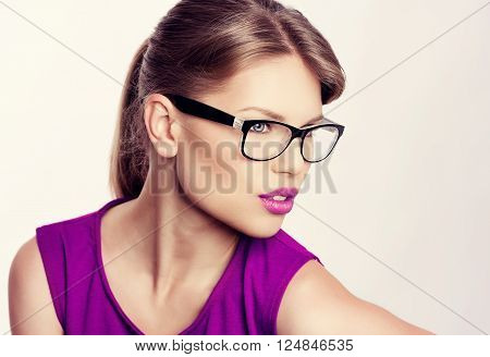 Close-up portrait of beautiful young blonde wearing stylish eyeglasses with purple lips. Attractive Caucasian businesswoman in spectacles.