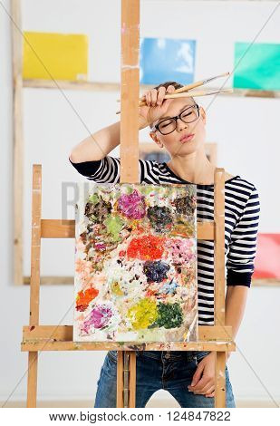 Young woman artist tired after drawing oil picture in her artistic studio. Portrait of professional female painter at work.