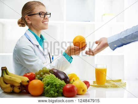 Smiling doctor nutritionist giving orange to male patient sitting at the desk with colorful fruits and vegetables. Concept of natural remedy and healthy lifestyle.