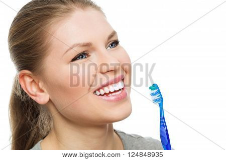 Dental care woman. Attractive female with healthy bright smile showing brush as symbol of oral hygiene.