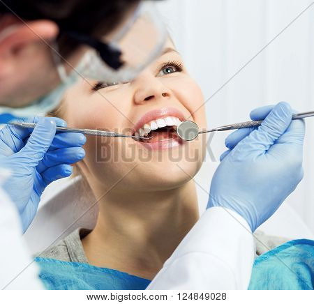 Dental health. Male hygienist examining patient teeth on caries. Young woman showing her teeth to doctor.