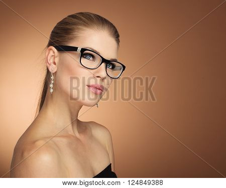 Fashion portrait of young glamour female in optical eyewear with black frame over golden background. Pretty girl with beautiful evening makeup wearing jewelery posing in studio.