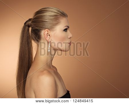 Portrait of fashionable young woman with long hair tail in profile. Serious elegant female wearing jewelery looking aside at space for text.