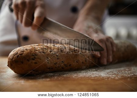 Close-up of baker hands cutting fresh bread from oven. Female cook in uniform preparing meal in restaurant kitchen.