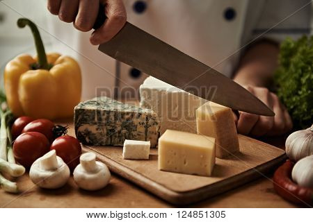 Chef hands cutting parmesan cheese on wooden board in the kitchen. Concept of cheese collection and mediterranean delicatessen.