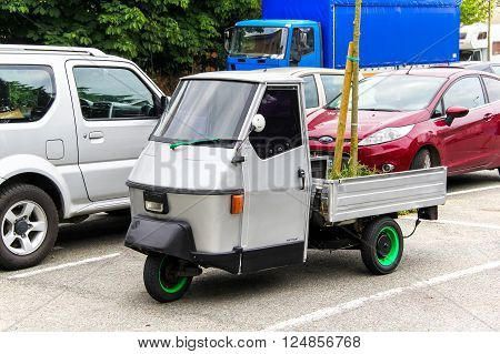 OVADA, FRANCE - AUGUST 7, 2014: Grey three-wheeled light commercial vehicle Piaggio Ape in the city street.