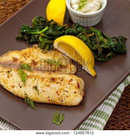 Baked Fish Fillet with Sauteed Spinach. Selective focus.