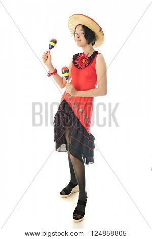 A pretty young teen dressed for celebrating Cinco de Mayo, looking at the viewer while shaking maracas.  On a white background.