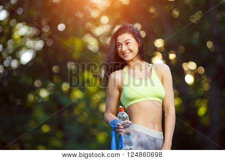 Fitness woman with a skipping rope and a bottle of water outdoors