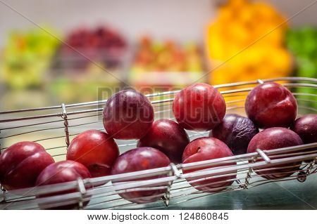 Plums in a bowl on a table on a self service breakfast counter in a hotel