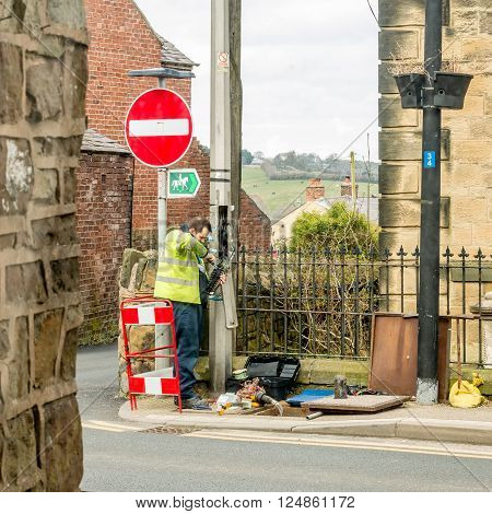 WREXHAM, WALES, UNITED KINGDOM - MARCH 21, 2016: Openreach workman fixing BT (British Telecom) telephone line outside in the street.