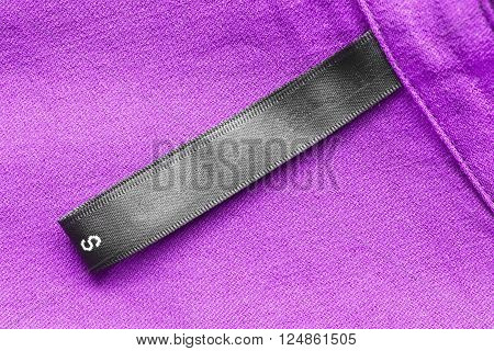 Blank black clothes label on purple cloth as a background