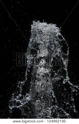 Fountain transparent water stream splash and drops in motion over black background