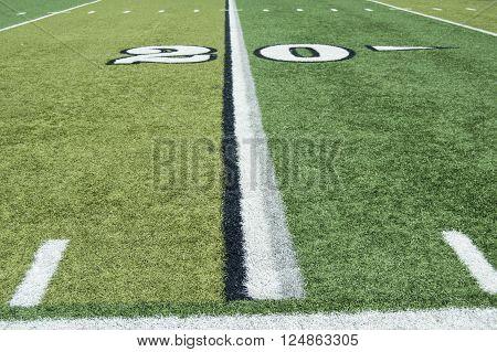Twenty yard line on a turf football field from the sideline.
