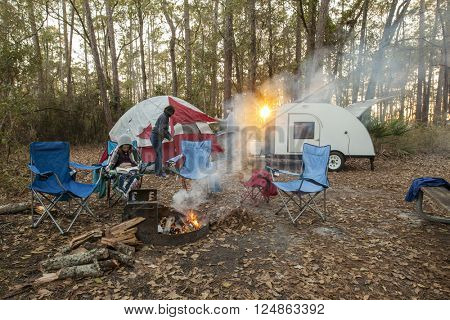 family setting up campsite at sunset with tent and teardrop trailer