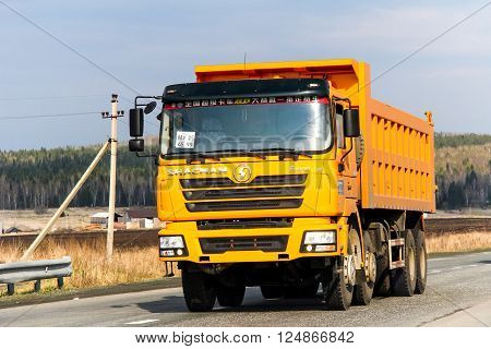 SVERDLOVSK REGION RUSSIA - MAY 8 2012: Yellow dump truck Shacman F3000 at the interurban road.