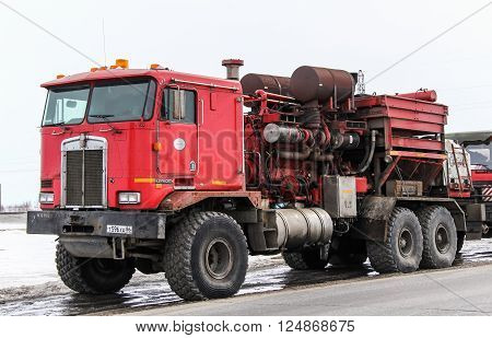 NOVYY URENGOY, RUSSIA - APRIL 20, 2013: Red gas and oil well service truck Kenworth C500K at the interurban road.